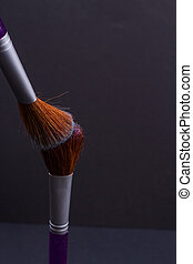 Two brown professional make up brushes on black background.