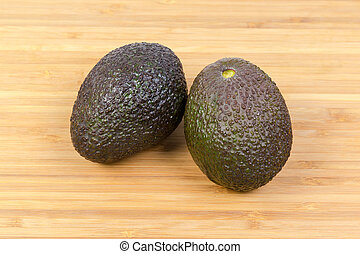 Two brown with green avocados on a wooden surface