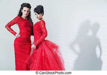 Two brunette girlfriends wearing red dresses
