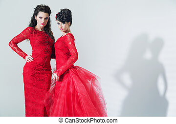 Two brunette girlfriends wearing red dresses