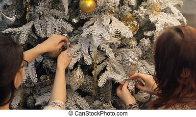 Two brunette woman in glasses fixed decorations on Christmas tree.