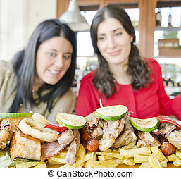 Two brunette woman ready for eat a lot of food