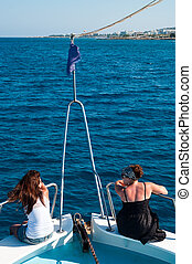 Two brunette women on bow of yacht in Mediterranean sea cruise