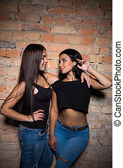 Two brunettes wearing black t-shirts and jeans