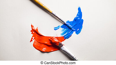 two brushes side by side with blue and orange paint