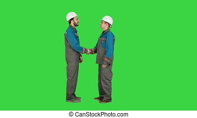 Two builder, architects handshaking on a Green Screen, Chroma Key.