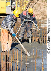 two builder workers during concrete works at construction ...