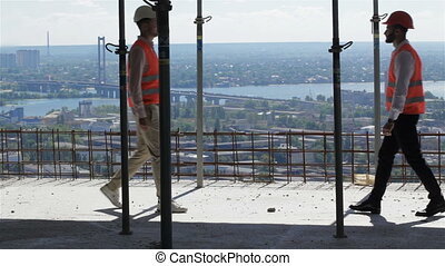 Two builders look at the river landscape from the building under construction