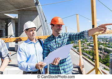 Two Builders On Construction Site Looking At Plans Contractor Meeting With Business Man