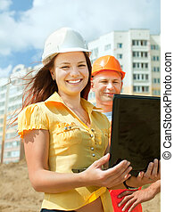 two builders standing at building site