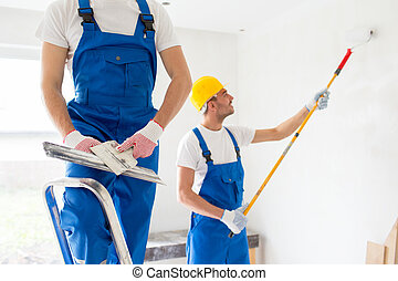 two builders with painting tools repairing room - building, ...
