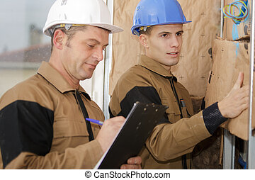 two builders working on a wall