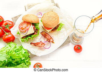 Two burgers served with glass of cola soda on white table
