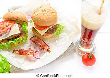 Two burgers served with glass of soda on white table