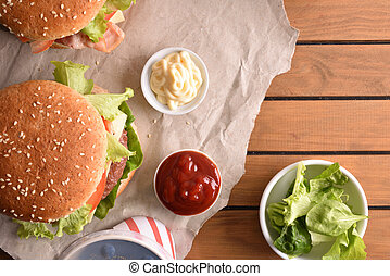 Two burgers with soda and souces on wood table background