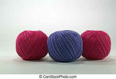 two burgundy and one lilac tangle of natural cotton thread for needlework on white background
