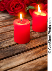 Two burning candles with fresh roses - Two red burning ...