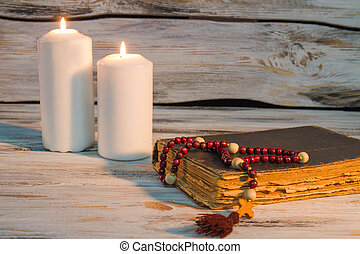Two burning canldes and holy bible with rosary.