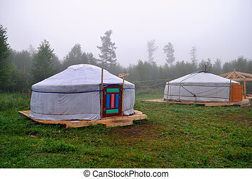 Two Buryat yurt in the background of the misty morning - Two...