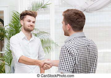 Two business colleagues handshake during meeting.