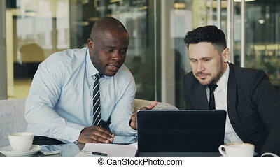 Two business colleagues looking at laptop computer and discussing their projects in modern office with glass walls. Bearded businessman and his partner sitting at table and talking