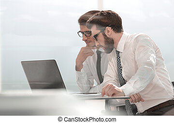 two business colleagues looking at the laptop screen