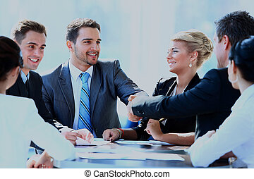 Two business colleagues shaking hands during meeting.