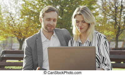Two business colleagues using laptop at the park together
