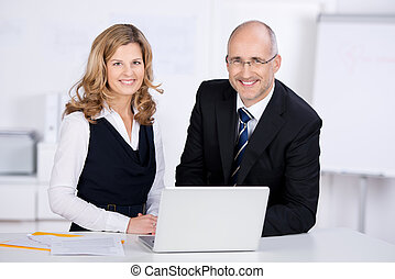 Two business colleagues with a laptop