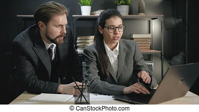 Two business colleagues working on laptop at office center