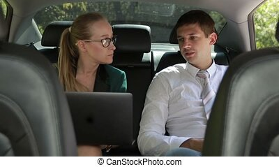 Two business colleagues working with laptop in car -...