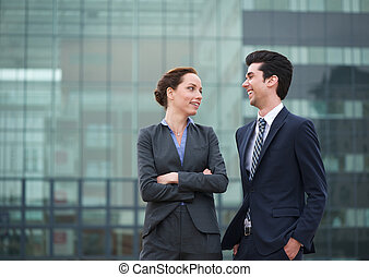 Two business collegues smiling outdoors in the city