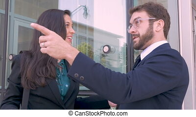 Two business executives celebrating success with a fist bump outside office