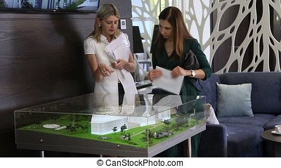 Two business girls looking at a mock office building in an office