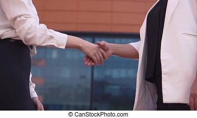 Two business girls shake hands. slow motion