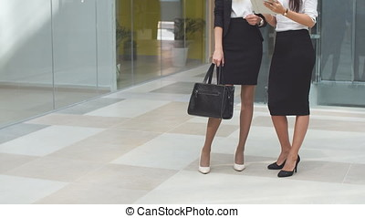 Two business girls using tablet computer in office building