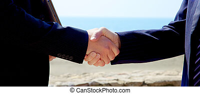 Two business hands shaking deal closed