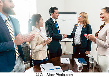 Two business managers shaking hands during meeting in the conferernce