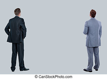 two business mans from the back - looking at something over a white background.
