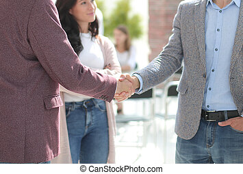 two business men shaking hands, greeting each other
