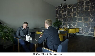 Two business men sit in a stylish cafe at a table.