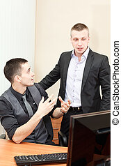 Two business men working together at office on computer