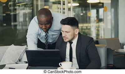 Two business partners discussing actively their startup project sitting in stylish cafe. Bearded businessman sitting ang talking his colleague while looking at laptop computer