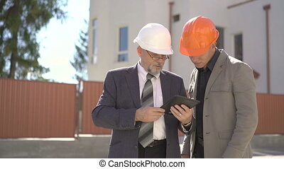 Two business partners looking on building plans on tablet. 4K