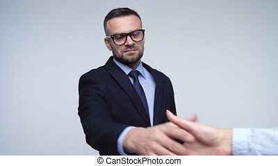 Two business partners shake hands welcoming each other in studio. Slow motion