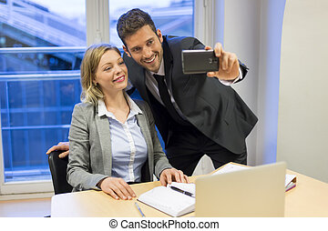 Two business peolpe do a Selfie in the office