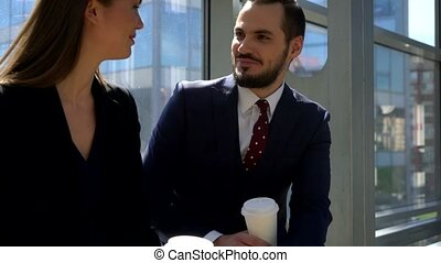 Two business people drink coffee