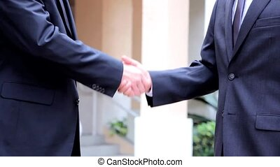 Two business people hand shake
