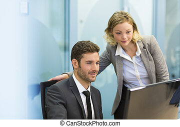Two business people in a office, working on computer