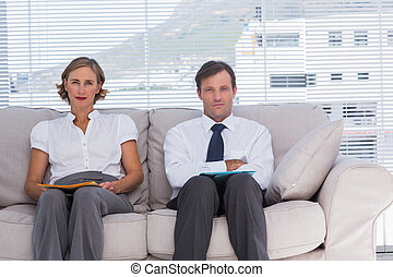 Two business people in a waiting room